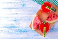 Vattenmelonsmoothies och skivor av den nya vattenmelon på en blå träbästa sikt för tabell Med stället för inskrift royaltyfri bild
