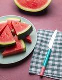 Vattenmelonstycken i en röd bakgrund royaltyfri bild