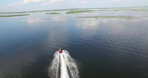 Vattenmotorcykeln svävar på den breda floden Reflexion av himmel arkivfilmer