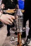 Vattenpipaserveren förbereder ett Shisha rör för att röka royaltyfria foton
