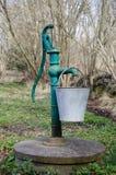 Vattenpump för gammal hand med en hink Arkivbilder