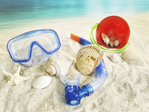 Vattenskyddsglasögon och leksaker i sanden Arkivbilder