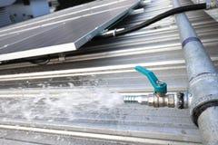 Vattenslanghaklapp för solpanellokalvård arkivfoto