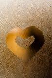 Vattensmå droppar med förälskelsehjärta formar på genomskinligt exponeringsglas Guld- abstrakt ram och flytande texturerad bubbla Royaltyfria Foton