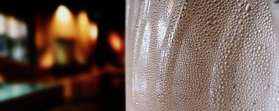 Vattensmå droppar på en flaska - kondensation mot en mörk bakgrund royaltyfri foto