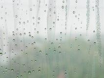 Vattensmå droppar på ett kallt fönster förser med rutor arkivfoton