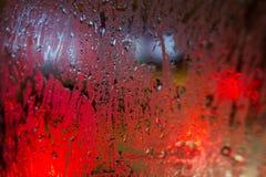 Vattensmå droppar på exponeringsglaset med en suddig bakgrund och en röd belysning, abstrakt textur, bakgrund Arkivbild