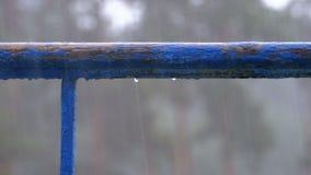 Vattensmå droppar som dryper med fönster, balkonger eller räcket mot bakgrunden av gatan, var det finns regn lager videofilmer