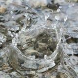 Vattensmå droppar som faller in i den lilla pölen av vatten som täcker små stenar som skapar invecklade färgstänkmodeller Arkivbild