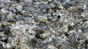 Vattensmå droppar som faller in i den lilla pölen av vatten som täcker små stenar som skapar invecklade färgstänkmodeller Arkivfoto