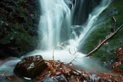 Vattensprej nedanför den lilla vattenfallet på bergströmmen, vatten faller över den mossiga stenblocket Sprejen skapar på nivån o Arkivfoto