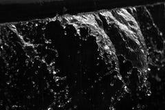 Vattensprej och färgstänk i svartvitt Arkivbild