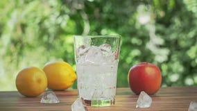 Vattensprej som häller i exponeringsglas som är fullt av iskuber, nära skott Gula citroner, rött äpple och iskuber på det bruna s stock video