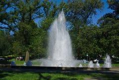 Vattenspringbrunn med några personer omkring på den soliga söndag eftermiddagen royaltyfri foto