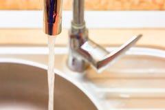 Vattenstråle från vattenkranen i diskhon arkivfoton