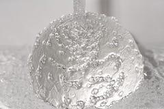 Vattenstrålen slår en glass boll arkivbilder
