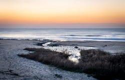 Vattenström in mot havet på solnedgången royaltyfri foto