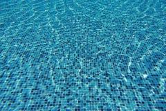 Vattenvåg i simbassäng med ljust reflektera vägg för textur för bakgrundstegelsten gammal arkivfoto