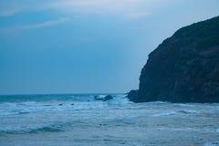 Vattenvågor på stranden som slår bergmist royaltyfria foton