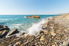 Vattenvågor som bryter på gravels, kiselstenar och stenblock av en tom strand i den hårda steniga kustlinjen av Liguria, norr Ita Arkivfoto