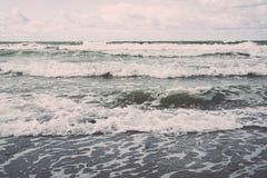 Vattenvågor som rusar i sand Arkivfoto
