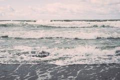 Vattenvågor som rusar i sand royaltyfria foton