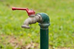 Vattenvattenkran med gräsbakgrund Royaltyfri Bild
