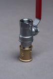 Vattenventil med det röda handtaget på grå färger Royaltyfri Fotografi