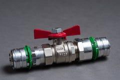 Vattenventil med det röda handtaget på grå färger Arkivfoton