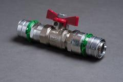 Vattenventil med det röda handtaget på grå färger Fotografering för Bildbyråer