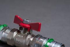 Vattenventil med det röda handtaget på grå färger Arkivfoto