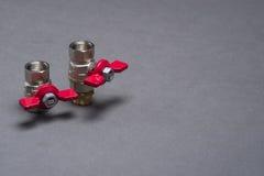 Vattenventiler med det röda handtaget på grå färger Arkivfoton