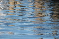 Vattenyttersida med blåttvågor och mörka reflexioner som en abstrac Royaltyfria Bilder