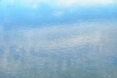 Vattenyttersida med färgreflexion för blå himmel i floden royaltyfri bild