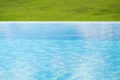 Vattenyttersida med grön gräsmatta runt om simbassäng royaltyfri foto