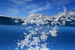 Vattenyttersida med vågen och bubblor Fotografering för Bildbyråer
