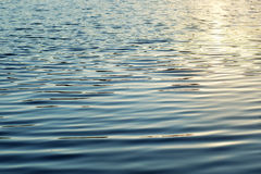 Vattenyttersidan som är upplysta vid solen, de ljusa vågorna och krusningarna på vattnet Arkivbilder