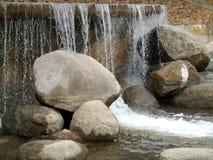 Vattnet och stenarna på vattenfallet Fotografering för Bildbyråer