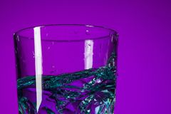 Vattnet som plaskar i exponeringsglas på lila bakgrund Royaltyfri Fotografi