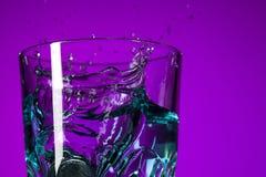 Vattnet som plaskar i exponeringsglas på lila bakgrund Arkivbild
