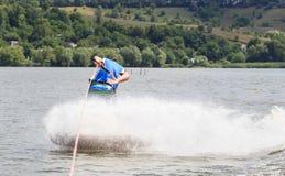 VATUTINE UKRAINA - JULI 15: Idrottsman nen tycker om wakeboarding och lagledaretrick på Juli 15, 2017 i Vatutine, Ukraina Arkivbild