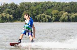 VATUTINE UKRAINA - JULI 15: Idrottsman nen tycker om wakeboarding och lagledaretrick på Juli 15, 2017 i Vatutine, Ukraina Arkivfoton