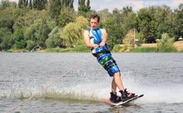 VATUTINE UKRAINA - JULI 15: Idrottsman nen tycker om wakeboarding och lagledaretrick på Juli 15, 2017 i Vatutine, Ukraina Royaltyfri Foto