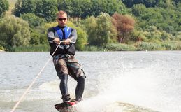 VATUTINE UKRAINA - JULI 15: Idrottsman nen tycker om wakeboarding och lagledaretrick på Juli 15, 2017 i Vatutine, Ukraina Royaltyfri Bild