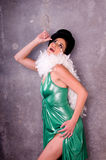 Vaudevillian. Vaudeville entertainer in a green metallic top hat and feather boa against a concrete wall Royalty Free Stock Image