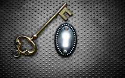 Vault key. Antique gold key and bright key hole on metal background Stock Photos