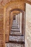 Vaulted arcades of Khaju bridge, Isfahan, Iran. Isfahan, Iran - Brick arched passage inside the stone bridge Khaju Royalty Free Stock Photo