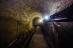 Vaulted underground tunnel  with electrical cables and rusty heating main pipeline Royalty Free Stock Photography
