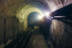 Vaulted underground tunnel  with electrical cables and rusty heating main pipeline.  Royalty Free Stock Image