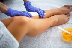 vax Ben för kosmetologWaxing Woman ` s i den Spa salongen arkivfoto